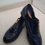 В наявності лакові туфлі-броги. Сині та чорні