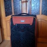 Чемодан среднего размера на колесиках. Черный с оранжевыми вставками.